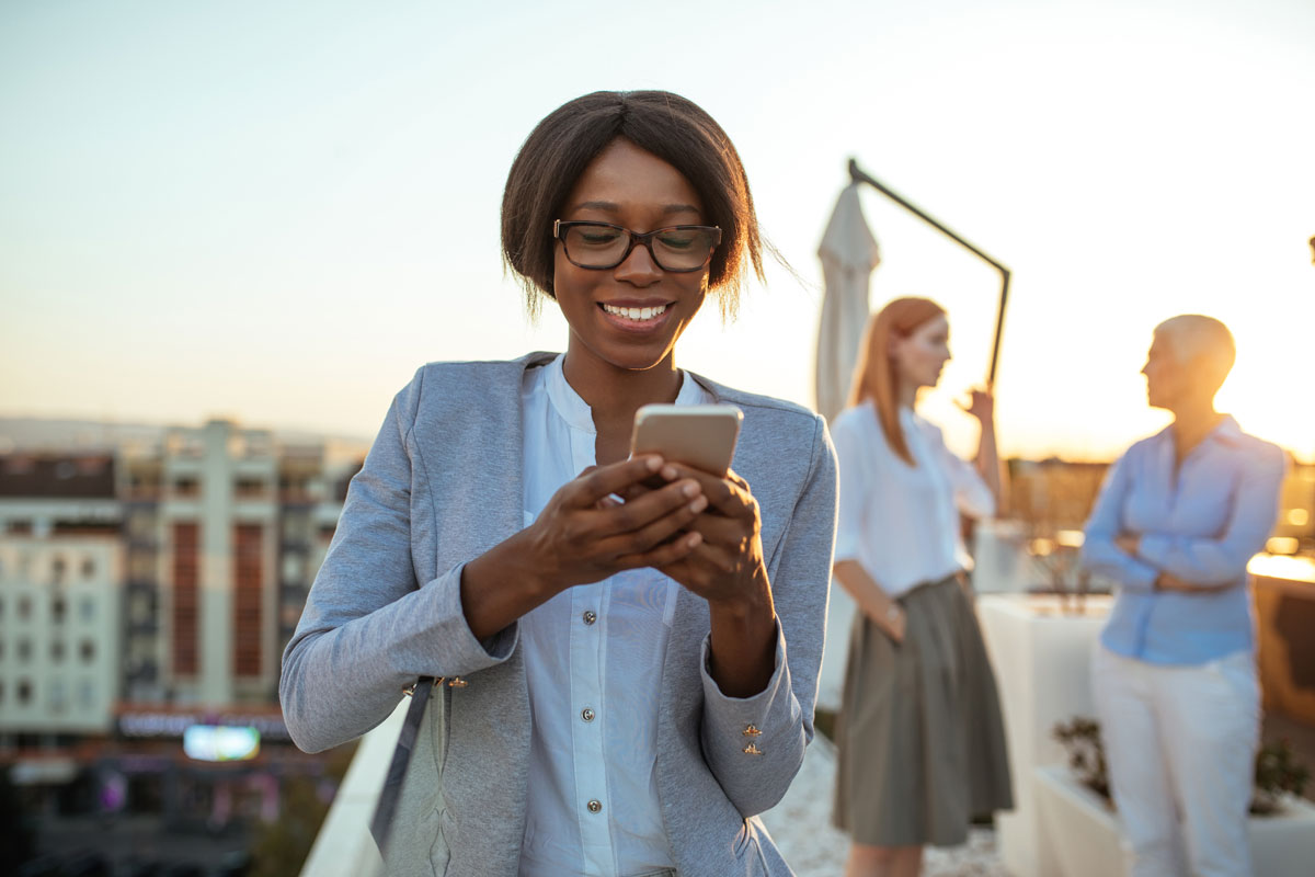 Young businesswoman holding a mobile phone. Her colleagues standing in the background